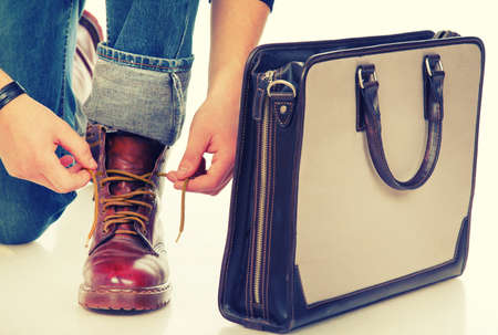 Close-up of a man lacing boots and a briefcase photo