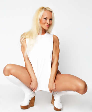 Blonde in a white dress sits photo