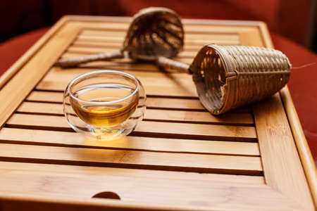 tea filter: Wooden tray with a teacup and two tea strainers Stock Photo
