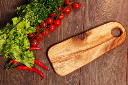 chopping board: Tomatoes, salad and parsley with a cutting board Stock Photo