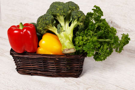 Wicker basket with broccoli, parsley and bell peppers photo