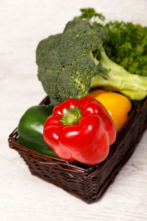Vegetables in a basket on a light wooden table  photo