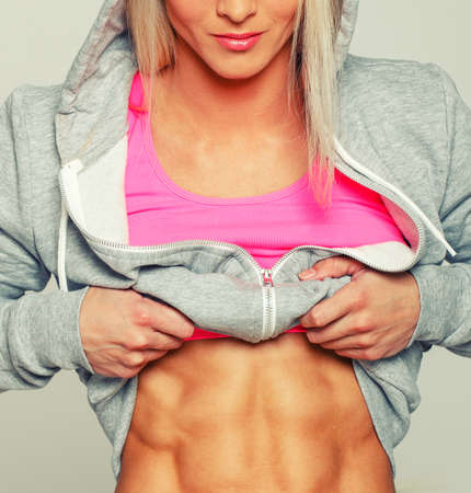 Blonde woman lifting up her hoodie to show ABS photo