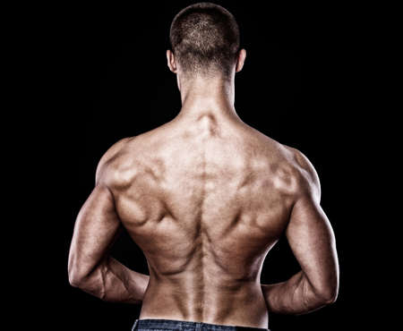 Portrait of sexy muscle man from back posing in studio