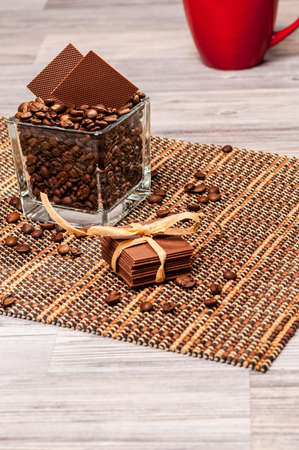Coffee beans and thin chocolate with a bow photo