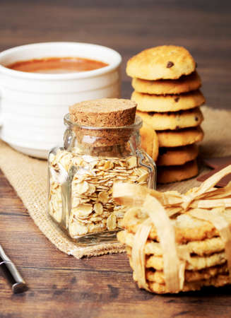 A cup coffee with some cookies and a jar of oats Stock Photo