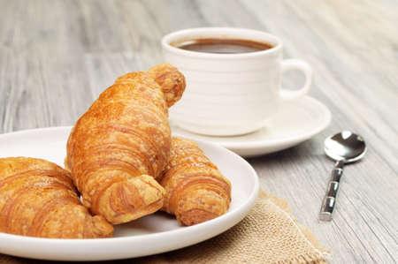Una taza de café y la placa con croissants