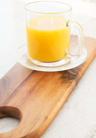 A chopping board with a mug of orange juice photo