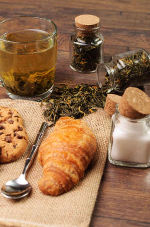 Croissant and jars of sugar and tea photo