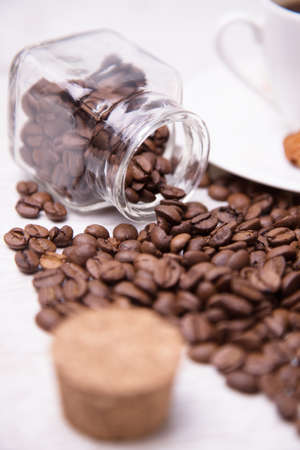 A glass jar and scattered coffee beans photo