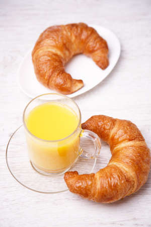 mig: A mig of juice and two croissants Stock Photo