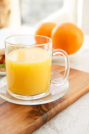 A cup of juice and oranges photo