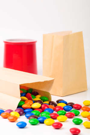 Paper bags with different color candies photo