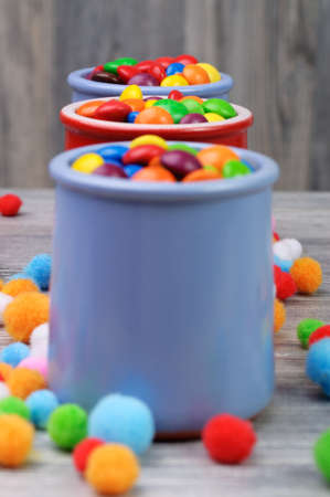Colorful candies in jars on a wooden background photo