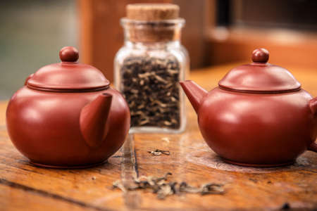 A rustic setting of two teapots and a jar of tea photo