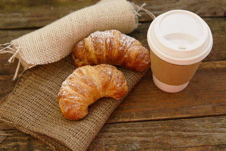 disposable cup: Two croissants and coffee-to-go in a rustic setting Stock Photo
