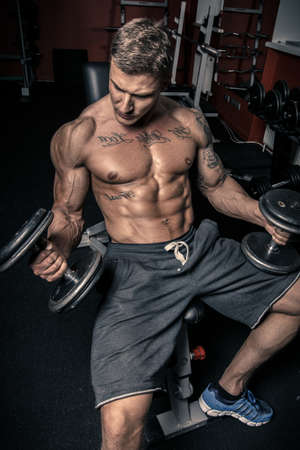 Guy in shorts with two dumbbells in a gym Stock Photo