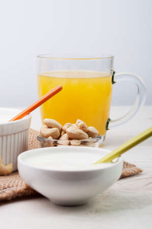 A cup of juice and white cream with cashew nuts photo