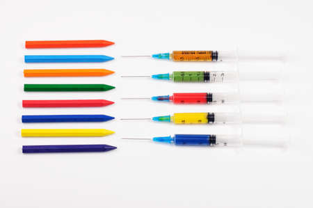 Colorful crayons and colorful syringes in front photo