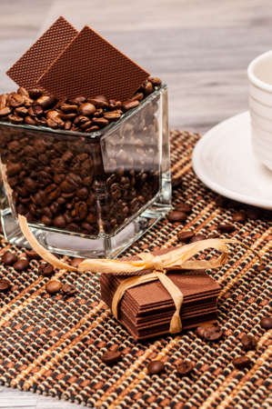 Stacked chocolate with a ribbon and coffee beans on a bamboo mat photo