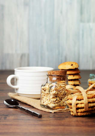 A jar of oats and cookis with ribbons with a cup