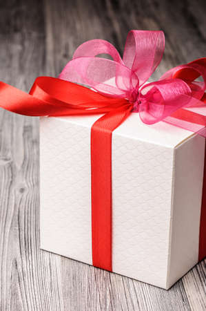 White textured gift box with red and pink ribbons photo