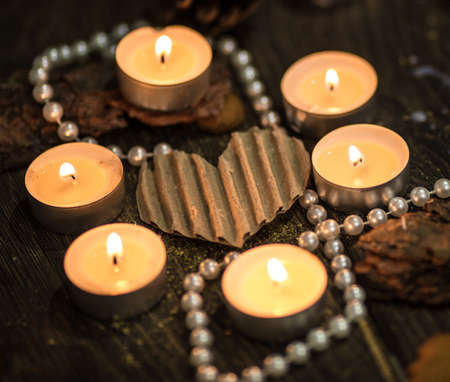 Pearls and candles around a paper heart photo