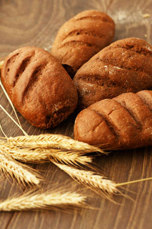Homemade bread and wheat ears on a wooden background photo