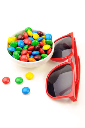 Red framed sunglasses and candies in a bowl photo
