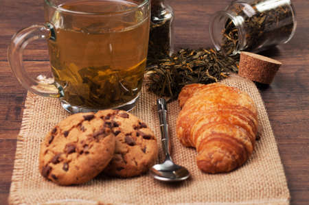 Chocolate chip cookies and a croissant with a cup of tea photo