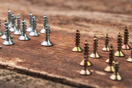 essentially: Divided golden and silver screws on the table
