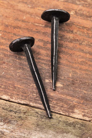 Two old nails on a wooden surface photo