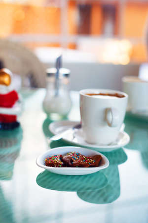 candes: Photo of  white cup with tasty coffee and some Christmas candys .Christmas mood. Stock Photo