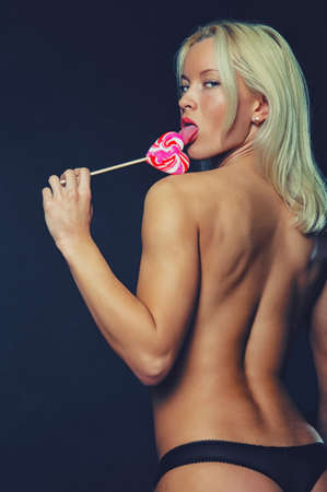 nude blond girl: Beautiful half-naked girl licks a lollipop