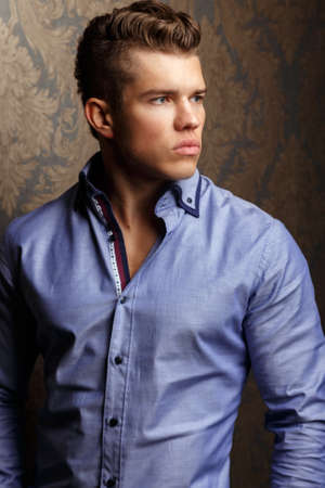 lips glow: Fashion portrait of man in shirt poses over wall