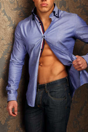 cheekbones: Fashion portrait of man in shirt showing his abs and poses over wall Stock Photo