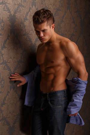 male body: Fashion portrait of man showing his muscular body and poses over wall Stock Photo