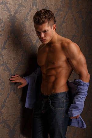 poses de modelos: Moda retrato del hombre que muestra su cuerpo musculoso y plantea sobre la pared