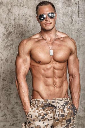 hombre desnudo: Retrato de la moda masculina muscular en gafas de sol sobre la pared