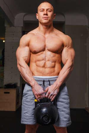 pezones: Hombre fuerte musculoso culturista muestra sus músculos que contienen la kettlebell
