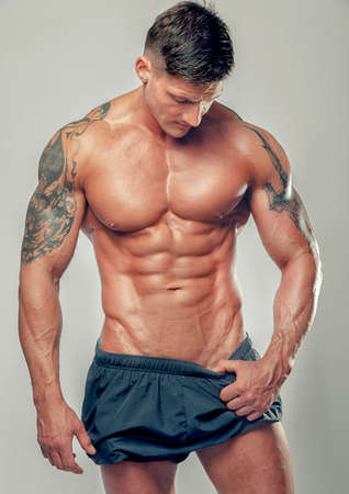 Strong muscular man bodybuilder poses and shows his muscles Stock Photo