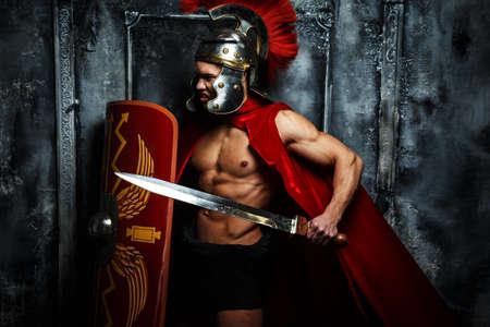 romano: Guerrero romano con cuerpo muscular que sostiene la espada y el escudo Foto de archivo