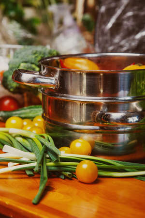 Image of vegetables on the table and in the stockpot Stock Photo