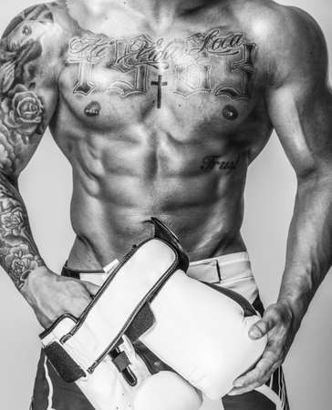 muscled: A muscled boxer with tattoos holding gloves