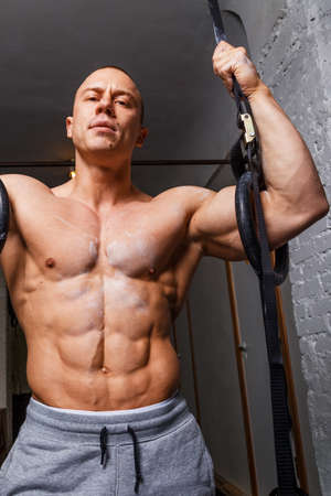 beefcake: Strong muscular man bodybuilder poses and shows his abs Stock Photo