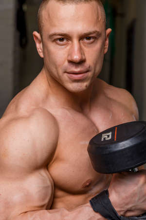 beefcake: Strong muscular man bodybuilder shows his muscles holding dumbbell Stock Photo