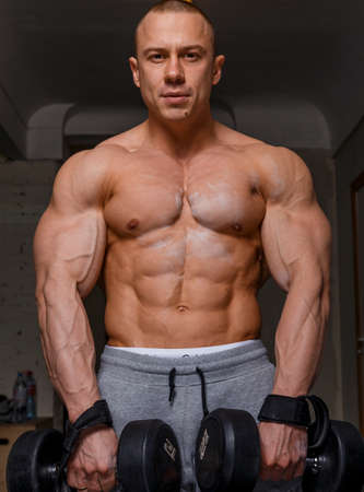 pectorals: Strong muscular man bodybuilder shows his muscles holding dumbbells Stock Photo