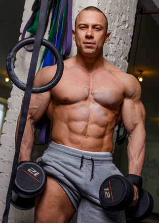 beefcake: Strong muscular man bodybuilder shows his muscles holding dumbbells Stock Photo