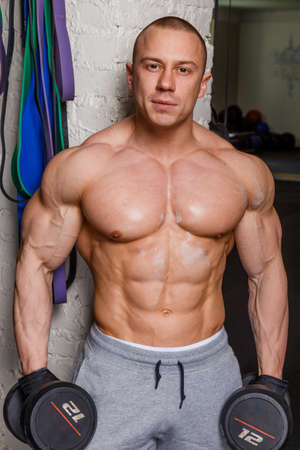 pezones: Hombre fuerte musculoso culturista muestra sus músculos que contienen pesas