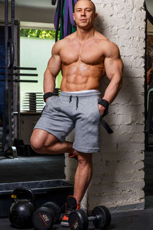 beefcake: Strong muscular man bodybuilder poses and shows his trunk Stock Photo